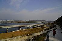 行人在郧阳岛立交桥边的山路上