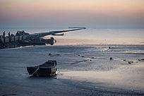 黎明时刻海边滩涂渔船海堤