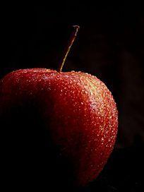 黑色背景灯光下的红苹果图片
