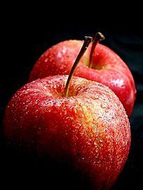 黑色背景下的两个红苹果局部图片