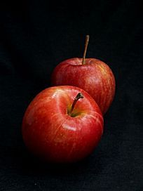 黑色背景下的两个红苹果图片