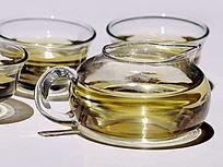 近拍灯光下的玻璃茶壶茶杯茶水特写图片