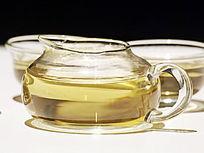 近拍灯光下的玻璃茶壶茶水特写图片