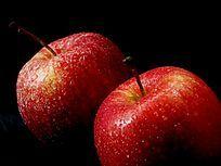 近摄黑色背景下的两个红苹果局部图片