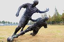 踢足球的两人雕塑