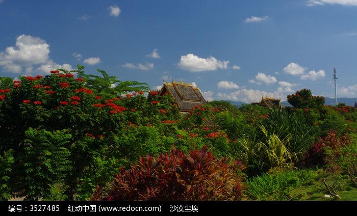 显露在绿荫花丛外的傣族竹楼屋顶