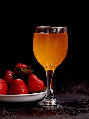 黑色背景一杯果汁和一盘草莓特写图片