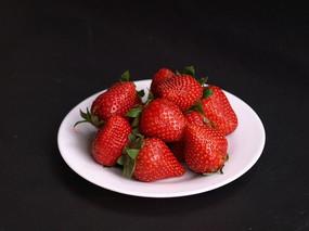 黑色背景一盘草莓特写图片