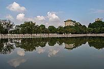 蓝天白云背景中水中倒影的武汉中南民族大学建筑和树林