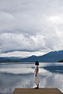 穿着白色裙子的短发女孩站在湖边