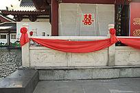 石柱围栏上的大红花和红绸带装饰物图片