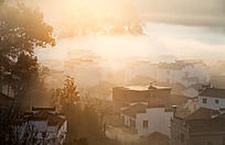 阳光透过晨雾炊烟的民居