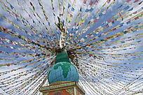 蓝天白云下古塔上悬挂的各色彩旗