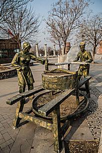 俩农民推磨雕塑 森林旁农民在耕地图片