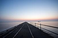 拂晓前长时间曝光拍摄深入海中的栈道
