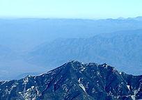突兀蓝色天空飘渺层叠群山空旷野山荒凉