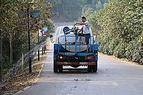 园林养护开着洒水车的树木浇灌水