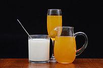 摆拍黑色背景玻璃杯里的果汁牛奶特写图片