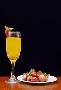 摆拍黑色背景草莓和高脚杯里的果汁特写图片