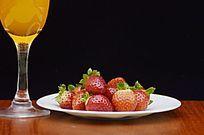摆拍黑色背景一杯果汁下的草莓特写图片