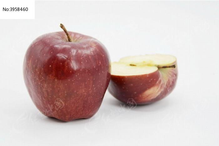 近拍一个红苹果边上放着切开的一半苹果特写图片图片