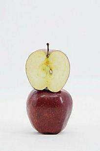 一个苹果上放着切开的一半苹果图片图片
