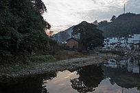 夕阳下小河倒映民居