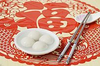 近摄中国剪纸上放着一双筷一碗汤圆特写图片
