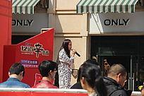 商业活动台上演唱歌曲的女孩