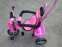 一辆三轮粉红色儿童推车