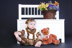 摸着脚丫拉着玩具熊的孩子