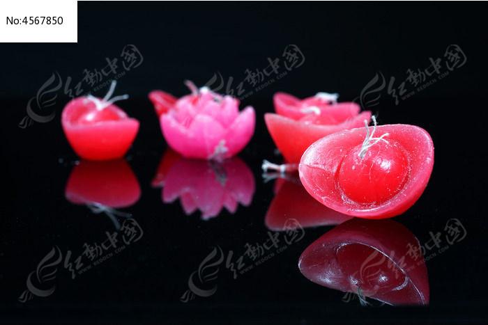 黑色背景上的元宝莲花造型的红色蜡烛图片