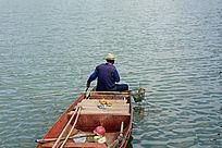 坐在船头清理河道的老人