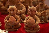 手抱寿桃的童男童女泥塑图片