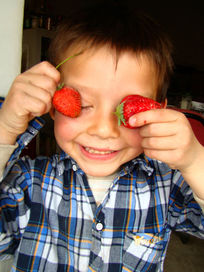 把两个草莓放眼睛上的儿童