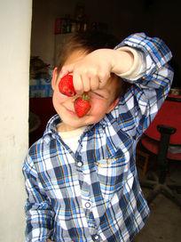 拿着两个草莓的孩子