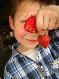 拿着两个草莓玩的孩子