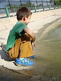 蹲在湖边玩水的孩子