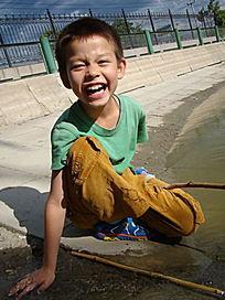 摸着水大笑的孩子