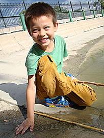 摸着水微笑的孩子
