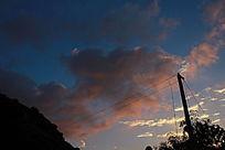 夕阳时的暗红云彩和蓝天与电线杆