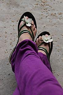 双腿交叉穿着花朵凉拖鞋的女人脚