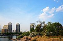 白云下的孟泰公园里的湖与树