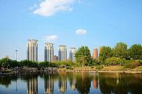 朵朵白云下的高层建筑与孟泰公园里的湖