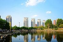 蓝天白云下的高层居民楼与孟泰公园里的湖