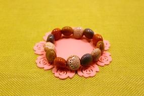 粉红色花朵杯垫上的火山石花釉椭圆形瓷珠手链