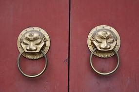 红色木门上的一对铜制门环