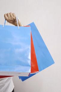 手提三个购物袋特写