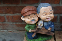 老爷爷推老奶奶坐木轮车卡通泥塑