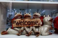 四只青蛙举欢迎牌的瓷雕